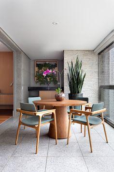 Churrasqueira área gourmet em varanda multiuso, com mesa redonda de madeira para quatro lugares, integrada com a sala, em apartamento que o casal adora madeira e cinza. #apartamento #decoração #apartamentoamplo #cinza #madeira