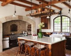 Super high ceilings with exposed beams give a traditional feel, and allow room for a big, chunky ladder to be hung from thick, black chain. Copper pots are stored on top. The most interesting feature of this room is the large, brick-lined niche that matches the arch of the window.