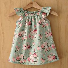Very pretty little girls vintage green and pink rose print cotton flutter sleeve peasant dress, with a matching elasticated knotted bow headband. The neckline is elasticated and the light weight poplin cotton fabric makes this little dress ideal for summer. To keep this
