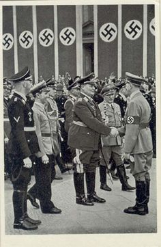 Hermann Göring shaking hands with Adolf Hitler while Heinrich Himmler and Joseph Goebbels look on