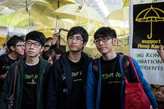 Umbrella Revolution Hong Kong, Student leaders Alex Chow (C), Nathan Law (L) and Eason Chung (R) are surrounded by pro-democracy protesters at the Hong Kong international airport before their scheduled flight to Beijing on November 15, 2014. Pro-democracy protest leaders say they will head to Beijing in hopes of bringing their demands for political reform to Chinese authorities. AFP PHOTO / ALEX OGLE (Photo credit should read Alex Ogle/AFP/Getty Images)