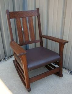 Gustav Stickley Tall Back Rocker. Nice form with stacked side stretchers. This has a reupholstered wrap around seat which is a chocolate brown leather. Dimensions are 38 tall, 22 1/2 deep, 26 1/2 across the arms, 29 1/2 deep to the rockers.