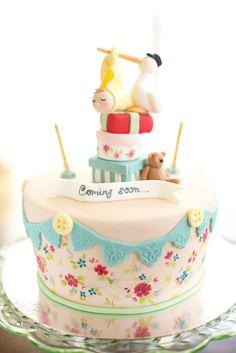 pastel de baby shower con decoraciones de flores y una cigüeña en la parte superior