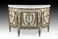 A Louis XVI style demie lune carved, silvered and grey lacquered commode, with white marble top.