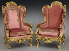 """Pr. French carved and gilt thrones with foliate and shell cartouche carved cresting over padded back and cushion with pink upholstery joined by high arms ending in scrolling handholds, both with gold applique to cushion front, one having additional applique to back and arm pads, seat rail and sides having shell cartouche decoration, raised on scrolling cabriole legs set on hoof feet. 54""""H x 32""""W x 26""""D, Circa - 19th C."""