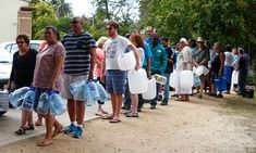 Residents queue to collect drinking water from a mountain spring collection point last month.