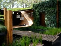 This photo shows an installation at the Melbourne International Flower and Garden Show. Designer James Dawson is flexing his green muscles in the varied plantings found here: vertical green, green roof and hanging plants. The shagginess of the Giant Liriope green wall anchors the space.