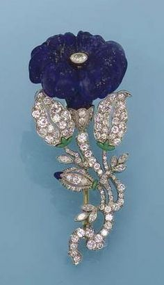 AN ART DECO LAPIS LAZULI AND GEM-SET FLOWER BROOCH/PENDANT, BY KOHN Designed as a carved lapis lazuli convulvulus to diamond and green enamel leaves, stem and bud, circa 1925, 6.0 cm long Signed Kohn