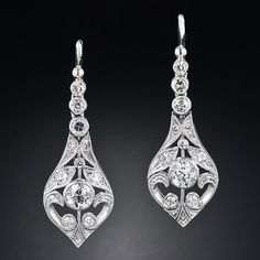 This elegant and timeless pair of diamond drop earrings was masterfully handcrafted in platinum by one of our finest jewelers. The graceful, curvaceous outline and consummate decorative open work is redolent of the exquisite feminine style of fine Edwardian jewels from the turn-of-the twentieth century. These ageless beauties glisten with one carat of bright-white, brilliant-cut diamonds for maximum sparkle, and measure 1 3/16 inches long by 3/8 inch wide.