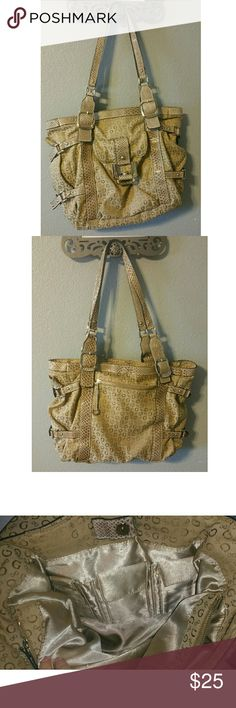 GUESS handbag Previously loved but in great condition! Camel colored purse by Guess. Champagne colored lining. Has snaps on the sides to make it bigger/smaller.  If you're looking for a bag with storage compartments, this is it! There are 4 pockets outside the purse. There's a big zippered pocket in the middle to divide the two sides of the purse. One side has 3 velcro pouches. The other side of the handbag has a small zippered pocket on the side, as well as 4 pockets underneath. Measures…