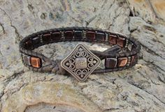 Jet black and burgundy metallic CzechMate beads on a single leather wrap bracelet with Toho seed beads and antique wilver filagree button