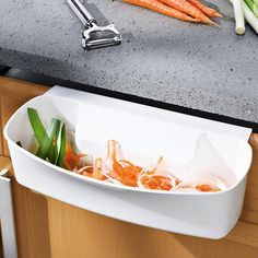 Einhängbarer Abfallsammler Schafft Platz auf Schneidbrett und Arbeitsplatte. Und hält Ihre Küche sauber.