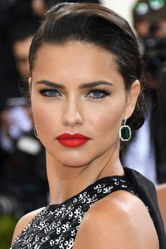 Red lip, lined eyes and brushed brows with a modern up do