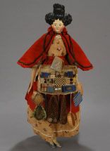 """15 1/4"""" German papier-mache (Kestner), as English Peddler, circa 1835. Details include wonderful facial features, rarer brown eyes, and a fabulous molded hairstyle with masses of side curls, and a braided """"Apollo's Knot on top of her lovely head. On a classic milliner's model style body of leather with wooden limbs, she """"wears"""" green-painted slippers on her carved wooden feet. Dressed in traditional street peddler garb, her costume includes a charming cotton print dress, an apron, plus a red…"""