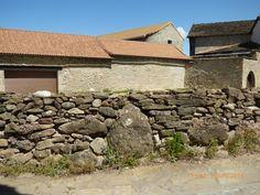 Menhir chico emparedado en muro de piedra seca.