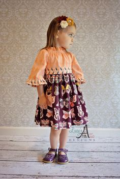 "The Betsy is one of our favorite fall styles! The Betsy dress is not your typical peasant style dress. It features a ruffled neckline, 3/4 belled sleeves, adorable pocket, and gathered skirt. My typical Betsy dress has a slim skirt, but this one features a fuller skirt and sash for a full yet fitted look. This goes perfect over a pair of tights and boots or leggings.Please state size in comments section at checkout!Size, Chest (finished), Length6-12 months, 21"", 17.5"