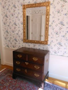 This classic burl front chest of drawers with willow mount handles pairs beautifully with an ornate gold wall mirror.