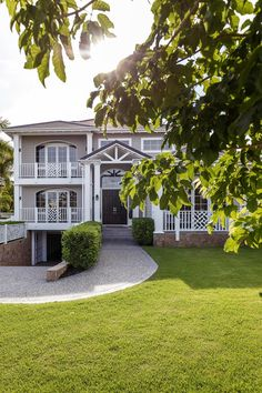 Grand Hamptons-style home exterior with white and grey and black door. Hamptons Style Homes, The Hamptons, Stone Gallery, Black Doors, Arched Windows, French Oak, Waterfront Homes, Step Inside