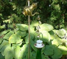 Vintage Coffee Pot Wind Chimes. Small Christmas Bells are tied to fishing line and are poured from the coffee pot spout into a lovely cup and saucer held up by a green bottle covered stake.