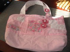 Handbag has an outside pocket in between the handles.   It has a pink corduroy bottom and a quilted stripe top.   the pocket and handles are decorated with button flowers.