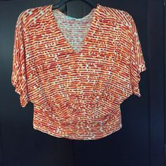 Beautiful orange and white print top Beautiful top with banded bottom hem. The print is gorgeous and perfect for spring Pleione Tops Crop Tops