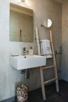 Μια ξύλινη σκάλα οδηγεί σε ένα πατάρι, όπου είναι το υπνοδωμάτιο του ζευγαριού, και ένα μπάνιο στρωμένο με τσιμεντοκονία.