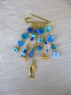 Kilt pin with blue buttons and beads; and gold charms