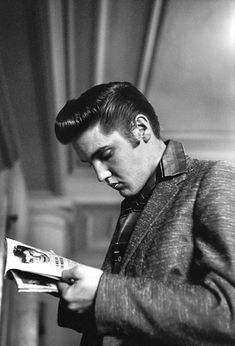 Elvis munches on a toothpick in the JeffersonHotel Coffee Shop near the magazine rack while he reads a story about Jerry Lewis, the comic.Richmond, VA June 30, 1956.