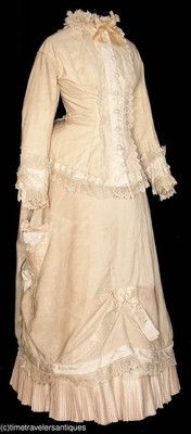 1882 lady's Summer cream silk two piece dress. A lined and stayed tunic style bodice with a bias cut bustle tail, passementerie button accents over the blind front hook and eye closure, trimmed in a pretty bobbin lace, with silk faille accents, piping, a silk neck bow, and bows at the cuffs. A polished cotton underskirt with a pleated hem, and a bunted bustle , draped accents with silk bows, and a fancy parasol pocket at one side.  Offered on Ebay