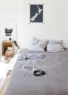 Scandinavian bedroom inspiration -  white walls + floors, grey bed linen, poster taped to wall, crate side table
