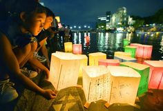 People release paper lanterns on the Motoyasu river facing the gutted Atomic Bomb Dome in remembrance of atomic bomb victims on the 69th anniversary of the bombing of Hiroshima