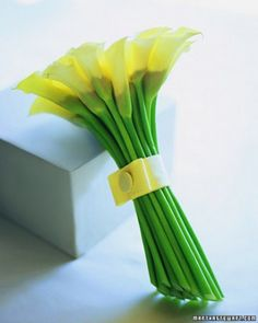 Photography: Victoria Pearson CONTEMPORARY BOUQUET A sheaf of miniature white calla lilies is perfect for a sophisticated bride. Flat on top and tapered at the bottom, this arrangement is designed so the stems make as strong a statement as the blossoms.