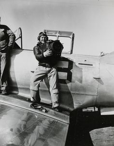 A U.S. Marine Corps photographer holding a Fairchild F-56 aerial camera posing on the wing of a trainer aircraft at the Naval Photography School in Pensacola, Florida.