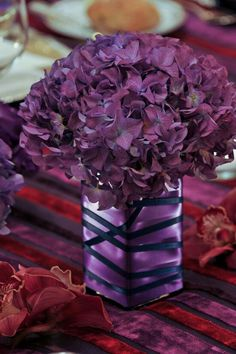 Purple centerpieces if you wrap it with ribbon you could use any container you wanted to hold the flowers, cuz you wouldn't see it and fake flowers would make this super cheap yee haw