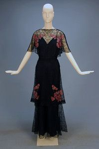 navy lace gown with printed chiffon appliques, 1930s allover floral lace with short butterfly sleeve, front boat neck with V-back, double tier skirt and self belt, having large rose pink and white floral appliques at shoulder and below hip both front and back.