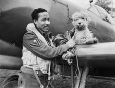 Flight Sergeant James Hyde, a fighter pilot serving with No 132 Squadron, Royal Air Force, pictured by a Supermarine Spitfire with 'Dingo', the squadron commander's pet dog, at Detling, Kent, England. Hyde, from San Juan, Trinidad, arrived in Britain more than two years previously to commence his training.