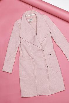 Schlicht und doch so sinnlich: Schon durch sein zartes Vintage rosa zieht der Mantel alle Blicke auf sich, ein hoher Stehkragen, sein langer Schnitt und ein offener Schlitz auf der Rückseite greifen den Purismus elegant auf.