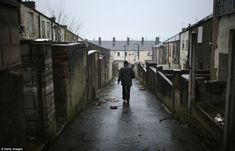 Depressing: A lone man walks down an alley separating two rows of terraces in Woodnook, Lancashire. There is no longer a demand for 'two-up, two-down' houses like these according to local councillor Clare Pritchard