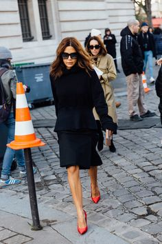 Christine Centenera in a black peplum jacket and black skirt and red pumps.