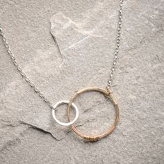 Freshie and Zero Love Necklace- Love leaves you hooked like this Love necklace by Freshie and Zero. Two silver and gold hoops are hooked together forever and dangle from a dainty chain. Its two tone style and modern design make it a great staple piece for any outfit.