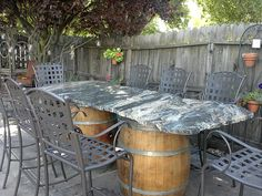 our table in backyard900lb granite slab with chiseled edges wine barrel legs steel frame under table and attched steel legs going thru wine barrels arched napa valley wine barrel table