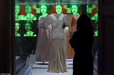 An exhibition assistant looks at a Bruce Oldfield dress that was worn by Princess Diana at Fashion Rules Restyled
