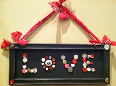 "Painted an old frame and back with black craft paint.  Lightly sanded edges for an ""old"" look and glued on all shapes/sizes of buttons to form the words LOVE.  Hung with a red hankerchief tied together.  All ready for Valentines Day!"