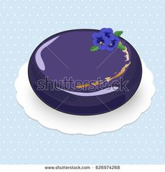 Picture of mousse cake with fruit filling decorated by gold and pansy flowers on the glossy glaze.The cake is on the blue polka dotted background.