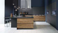 Zwarte, moderne keuken met hout. Deze moderne keuken bevat het perfecte contrast tussen donker en licht in deze keuken. De hoge kasten en de kast met schuifdeur in een mat zwarte kleur zorgen voor een speciaal contrast met de houten keukenkasten. De keuken heeft een asymmetrische U-vorm waardoor het een echte design look krijgt. De gehele keuken is ook volledig greeploos. Het zwarte werkblad loopt verder uit waardoor het kan gebruikt worden als een toog om aan te dineren.
