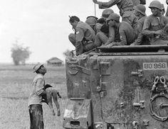 Foto de Horst Faas. Un padre muestra el cadáver de su hijo a un patrulla de Vietnam del sur. El niño murió mientras las fuerzas gubernamentales avanzaban hacia las posiciones de la guerrilla, cerca de la frontera con Camboya. La imagen, tomada el 19 de marzo de 1964, fue una de la que le valió su primer premio Pulitzer.