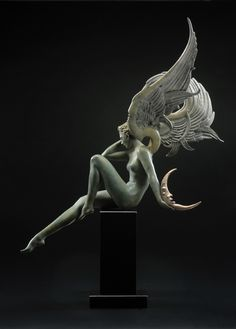 """""""Moonstruck - 2011"""" by Michael Parkes: """"The power of the new moon, and the beauty of the earth bathed in moonlight are very difficult subjects to portray in a painting, much less a sculpture. In Moonstruck, the sleeping angel represents the dappled calm of the night sky. She holds a shining moon in her hand while the North Star shimmers under her wing."""""""