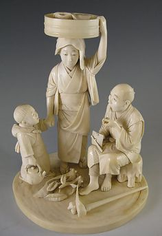 "Ivory Okimono of a Family This is a charming Tokyo school ivory okimono of a woman and child bringing lunch to the father during his work day. She balances a wonderfully modelled food basket overlaid with a sheer napkin covering the lunch on her head - a marvelous feat achieved by the sculptor. The child carries a tea kettle in one hand, his mother's hand in the other. ""Seishu"" etched signature within red cartouche and carved foliage can be found on the base. Height: 7.5"" Meiji Period, Japan"