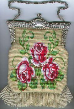 Triple Rose Art Nouveau purse.  The pearl bead background sets off to perfection a flowing design of three magnificent red, white, and pale pink-lavender roses accented by green leaves.  The silver nouveau design frame is in wonderful condition. The chain is made of silver cut-out charms, irises and possibly tulips, and at the ends of the chain, larger fleur-di-lis.  The lining is chamois leather and is in mint condition.