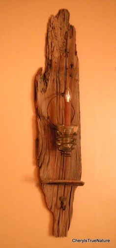 This barn wood wall sconce was created with 1800s lumber accentuating the natural worm holes and live edge. Highlights of the wood were left in as close to original color as was possible with its amazing blend of burnt umber, beige and gray. The naturally rusted vintage bed spring, which hangs from the original barn cut nail, was rescued from an old hunting camp deep in the Endless Mountains of Pennsylvania. A primitive electric line glass insulator holds the battery operated cinnamon…